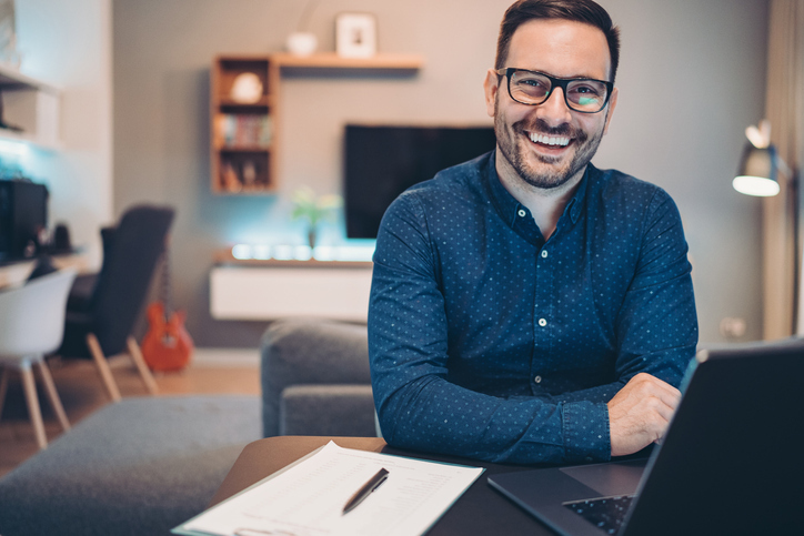 happy man at desk reviewing investment portfolio