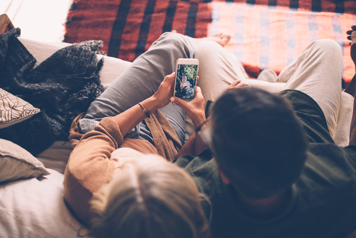 couple on couch looking at smart phone
