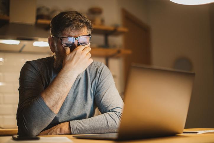 man at table looking at computer screen